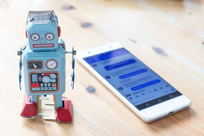 Kleiner Roboter neben einem Chatverlauf auf einem Smartphone.