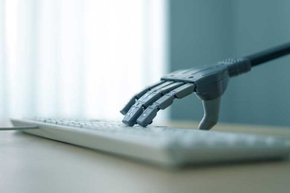 Robot hand typing on a keboard.